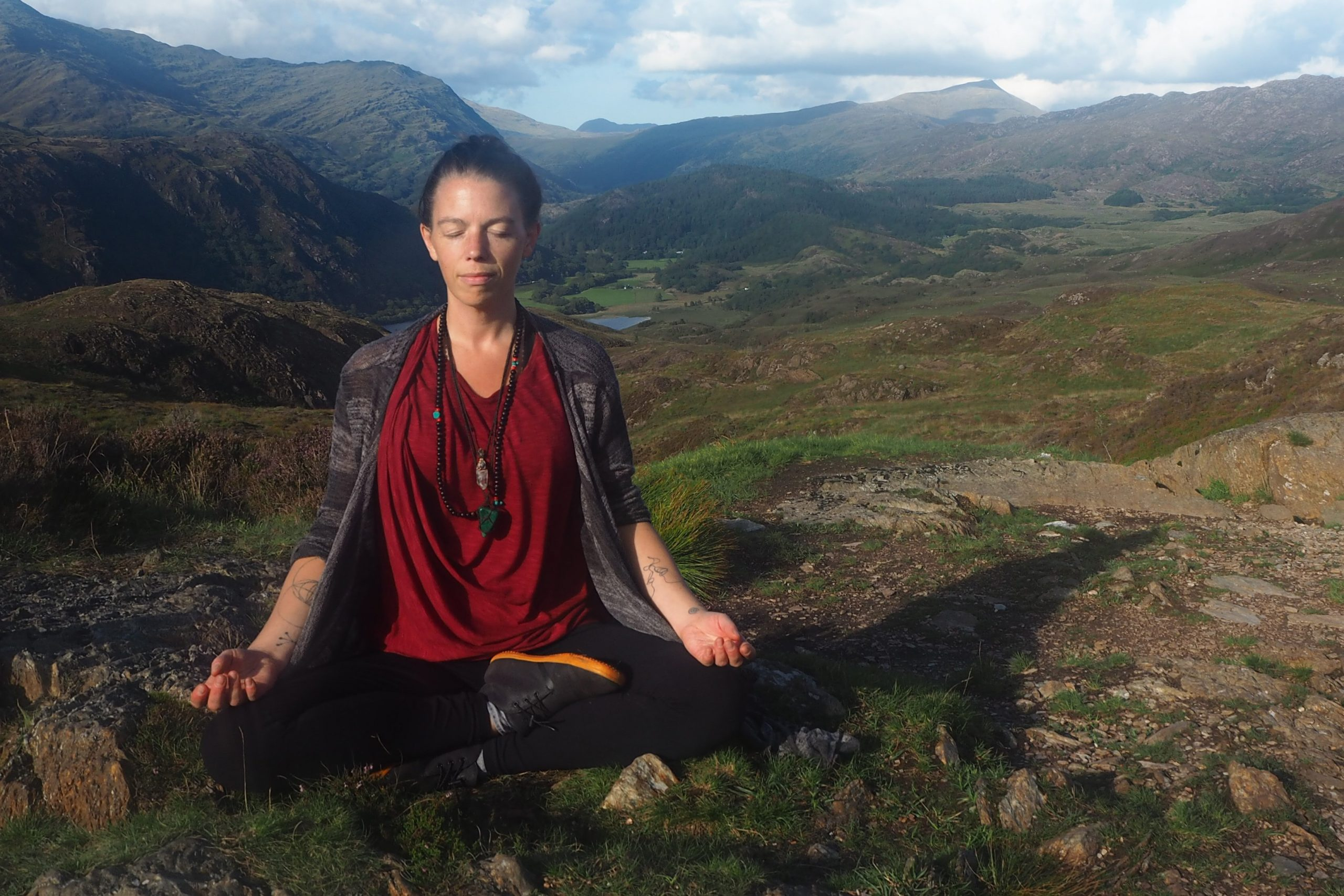 Gillian Torres of Mindfulness Liverpool practicing mindfulness on a hillside.