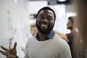 A happy man in a workplace. Mindfulness Liverpool offer courses and training in mindfulness and well-being for workplaces.